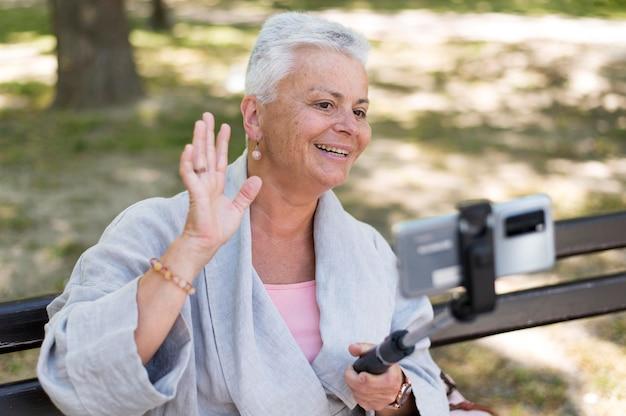 Średni strzał szczęśliwa kobieta biorąca selfie