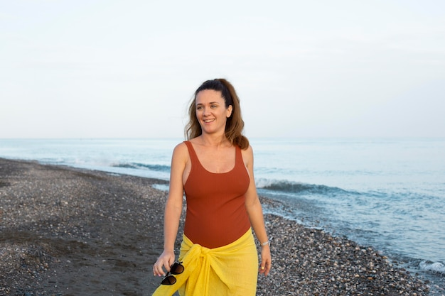 Średni strzał szczęśliwa kobieta na plaży