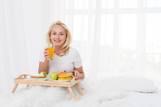 Średni strzał szczęśliwa kobieta pije sok pomarańczowego