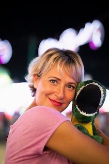 Średni strzał szczęśliwa kobieta ściska dinosaur zabawkę