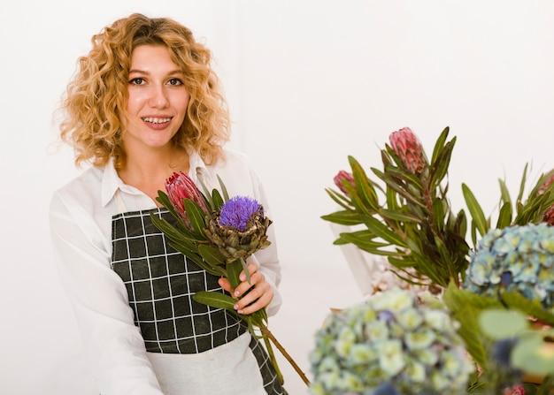 Średni strzał szczęśliwa kobieta trzyma kwiaty