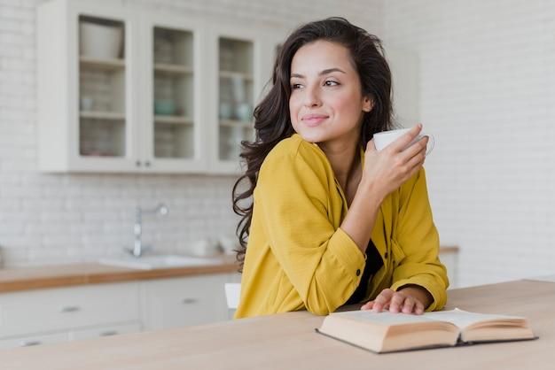 Średni strzał szczęśliwa kobieta z książką patrzeje daleko od
