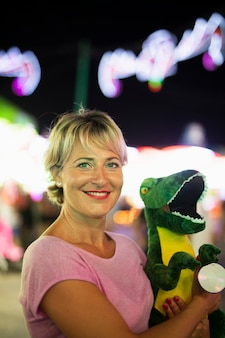 Średni strzał szczęśliwa kobieta z zabawką dinozaura