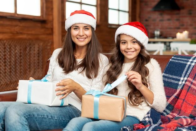 Średni strzał szczęśliwa matka i córka z prezentami