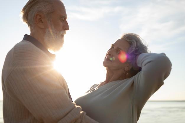 Średni strzał szczęśliwa para na plaży