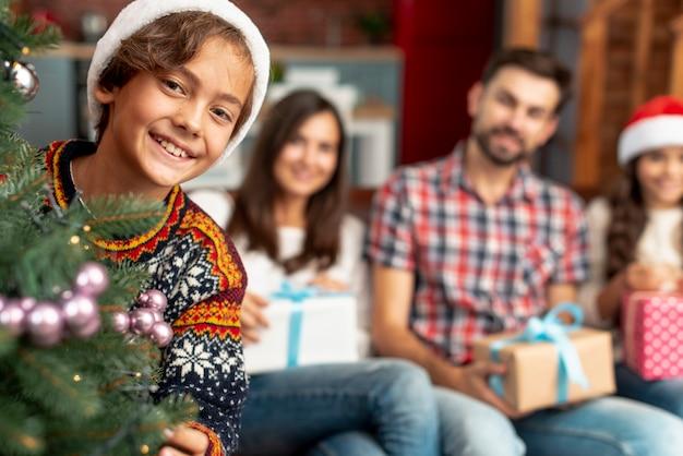 Średni strzał szczęśliwa rodzina siedzi w pomieszczeniu