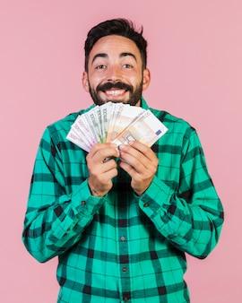Średni strzał szczęśliwy facet trzyma pieniądze
