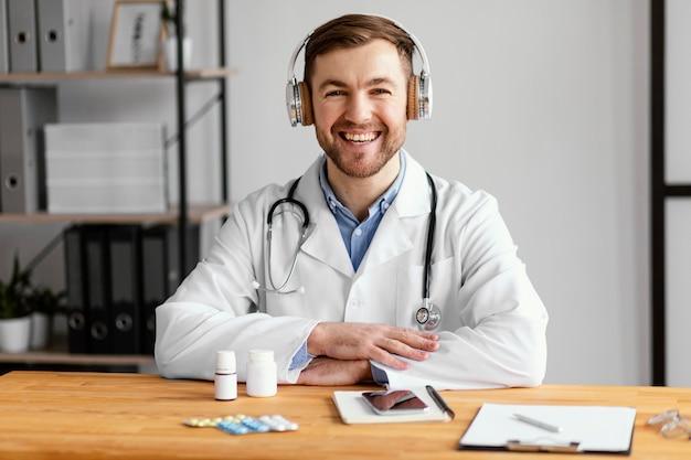 Średni strzał szczęśliwy lekarz przy biurku