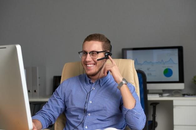 Średni strzał szczęśliwy menedżer pracujący w call center