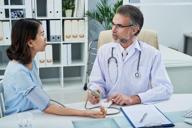 Średni strzał terapeuty mierzącego krew [uspokojenie pacjenta podczas konsultacji