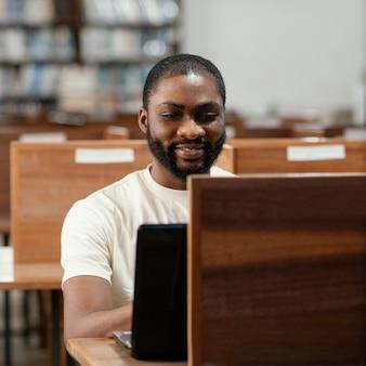 Średni strzał uczeń pracujący z laptopem