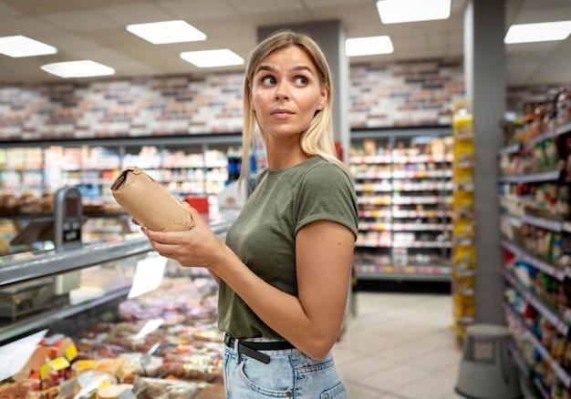Średni strzał uśmiechniętej kobiety trzymającej produkt