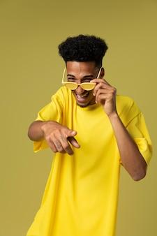 Średni strzał uśmiechnięty mężczyzna trzymający okulary