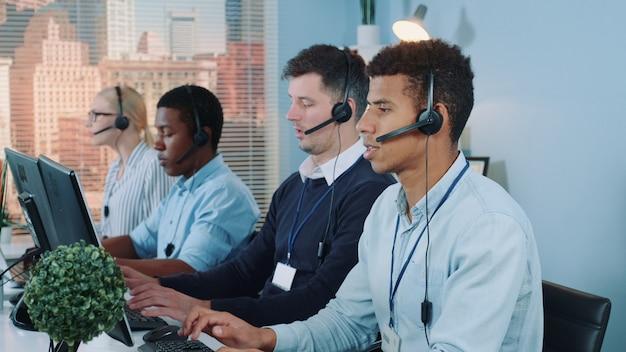 Średni strzał wielorasowych agentów call center rozmawiających z klientami w zestawie słuchawkowym