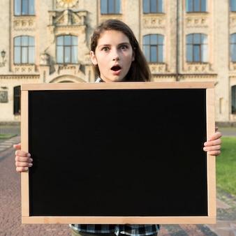 Średni strzał zaskakujący highschool dziewczyny mienia blackboard
