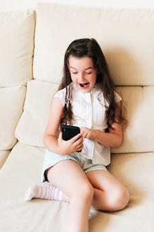 Średni strzał zdziwiona dziewczyna z telefonem na kanapie