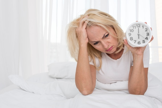 Średni strzał zmęczony kobiety mienia zegar