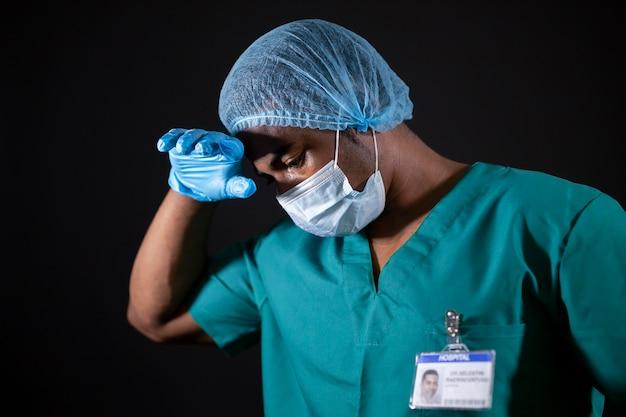 Średni strzał zmęczony lekarz z maską