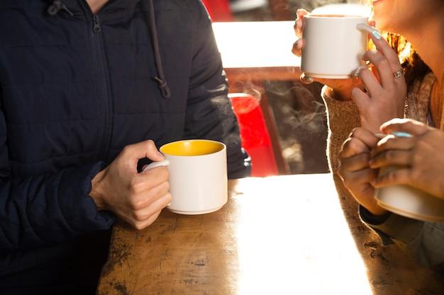 Średni strzał znajomych pijących kawę