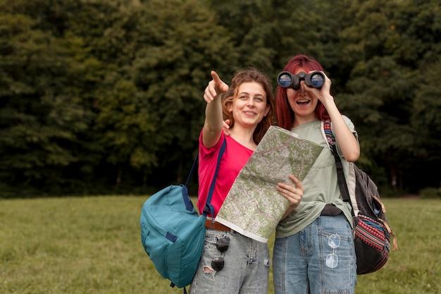 Średni strzał znajomych z lornetką i mapą w naturze