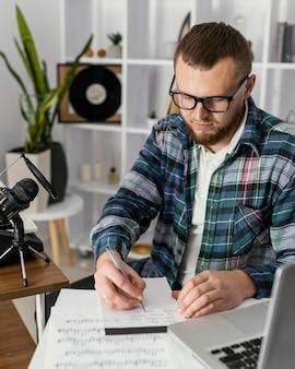 Średni ujęcie kompozytora piszącego na notatniku