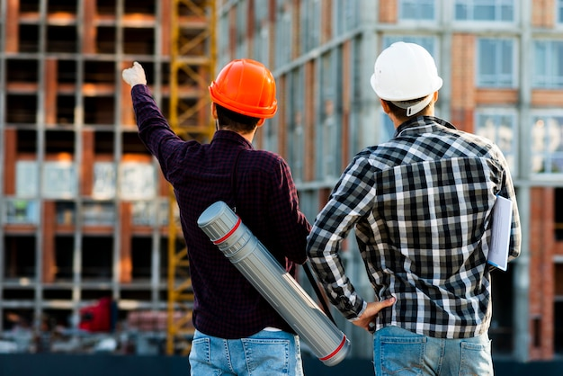 Średni widok z tyłu inżyniera i architekta nadzorującego budowę