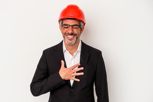 Średni wiek architekta kaukaski mężczyzna na białym tle śmieje się głośno trzymając rękę na klatce piersiowej.
