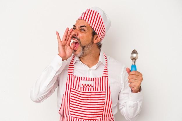 Średni wiek kaukaski producent lodu kaukaski mężczyzna trzyma łyżkę na białym tle krzycząc i trzymając dłoń w pobliżu otwartych ust.