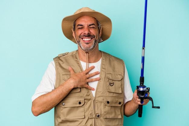 Średni wiek kaukaski rybak trzymający pręt na białym tle na niebieskim tle śmieje się głośno trzymając rękę na klatce piersiowej.