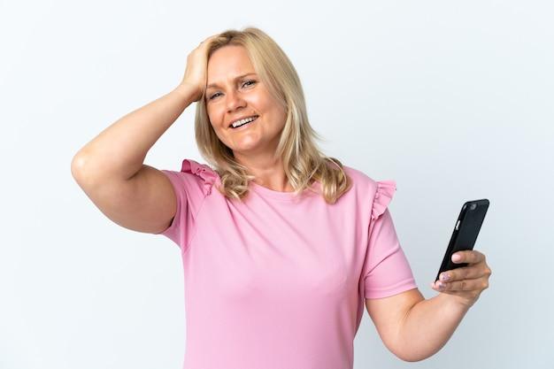 Średni wiek korzystający z telefonu komórkowego na białej ścianie coś sobie uświadomił i zamierzał znaleźć rozwiązanie