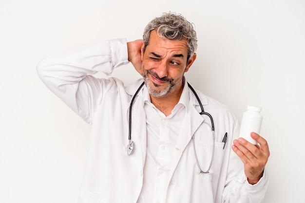Średni wiek lekarz kaukaski mężczyzna na białym tle dotykając tyłu głowy, myśląc i dokonując wyboru.