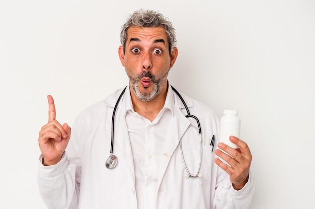 Średni wiek lekarz kaukaski mężczyzna na białym tle o jakiś świetny pomysł, pojęcie kreatywności.