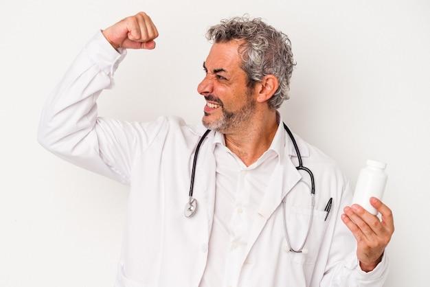 Średni wiek lekarz kaukaski mężczyzna na białym tle podnosząc pięść po zwycięstwie, koncepcja zwycięzca.