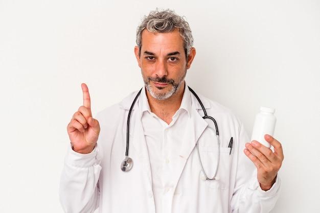 Średni wiek lekarz kaukaski mężczyzna na białym tle pokazując numer jeden z palcem.
