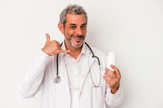 Średni wiek lekarz kaukaski mężczyzna na białym tle pokazujący gest połączenia z telefonem komórkowym palcami.