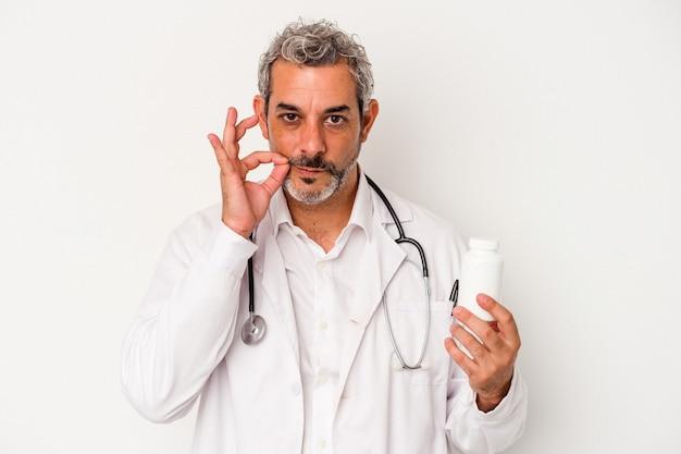 Średni wiek lekarz kaukaski mężczyzna na białym tle z palcami na ustach zachowując tajemnicę.