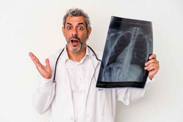 Średni wiek lekarz kaukaski mężczyzna trzyma radiografię na białym tle zaskoczony i zszokowany.