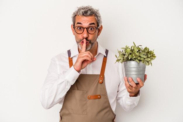 Średni wiek ogrodnik kaukaski mężczyzna trzyma roślinę na białym tle dochowując tajemnicy lub prosząc o ciszę.