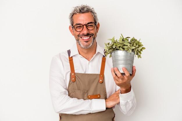 Średni wiek ogrodnik kaukaski mężczyzna trzyma roślinę na białym tle śmiejąc się i zabawę.