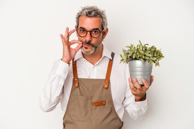 Średni wiek ogrodnik kaukaski mężczyzna trzyma roślinę na białym tle z palcami na ustach zachowując tajemnicę.
