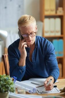 Średni zbliżenie mężczyzna robi korekty projektowi przy pracą
