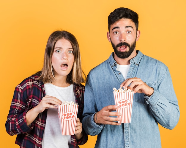 Średnia strzał zszokowana para z popcornem