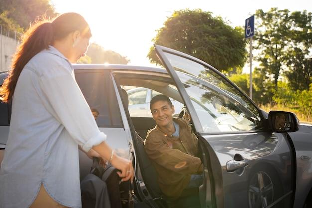 Średnia uśmiechnięta para z samochodem