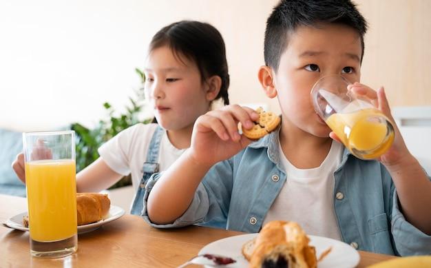 Średnie dzieciaki z sokiem pomarańczowym