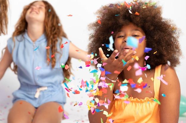 Średnie dziewczyny bawiące się konfetti