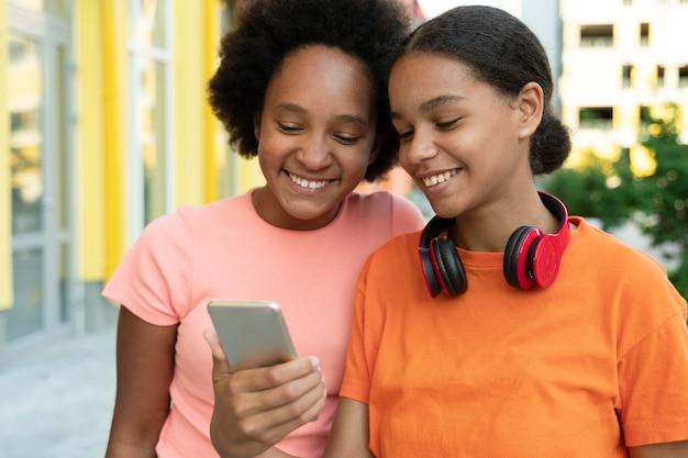 Średnie dziewczyny patrzące na telefon
