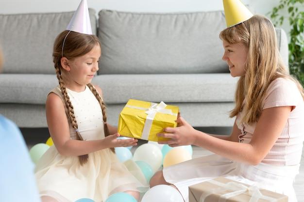 Średnie dziewczyny trzymają prezent