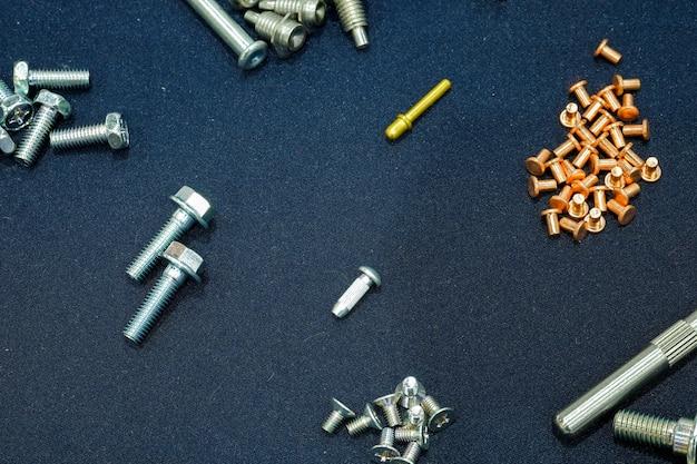 Średnie przemysłowe i małe sęki, nałożone na niebiesko-czarny materiał na widok z góry.