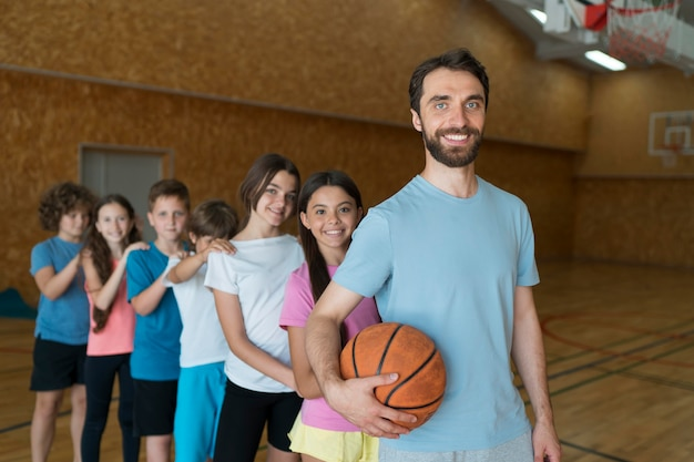 Średnie strzały dla dzieci i nauczyciela z koszykówką basket