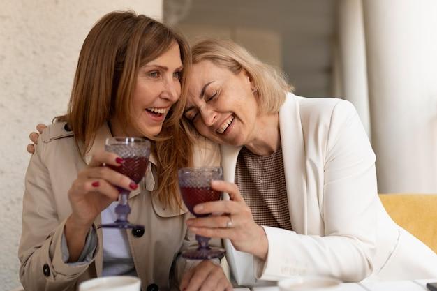 Średnie strzały szczęśliwe kobiety z napojami